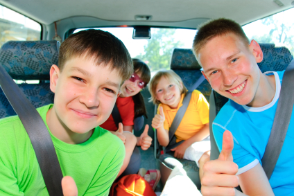 four kids in a car in bright clothes with seat belts on, smiling and happy