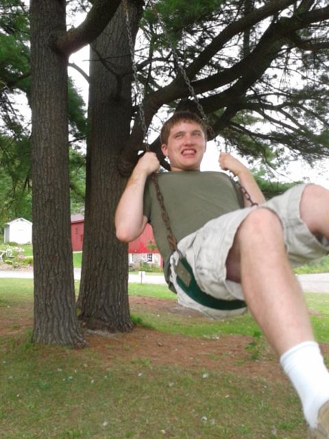 Smiling teenage boy on swings